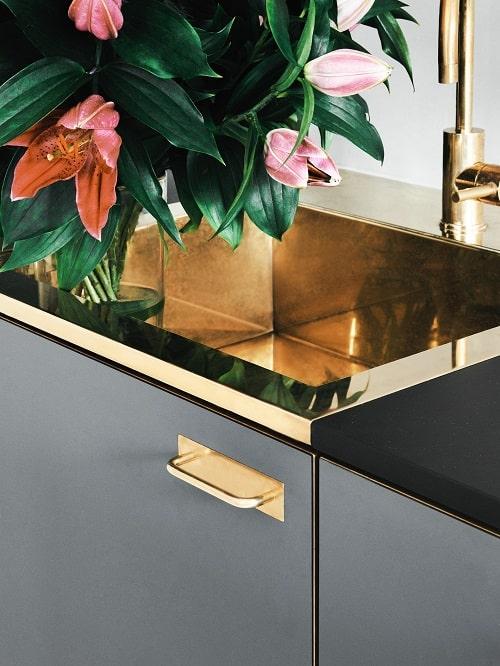 Design interior bucatarie gri inchis cu elemente metalice aurii si chiuveta aurie